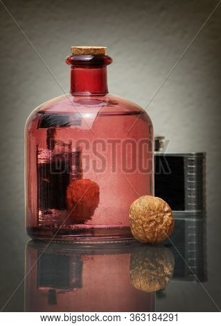 Still Life With Transparent Glass Bottle, Black Vintage Hip Flask, And Walnuts Against A Low Key Bac
