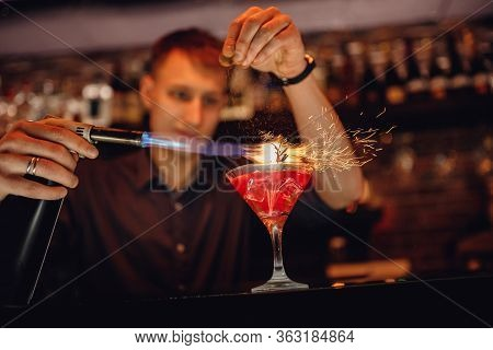 Barman Prepares Red Cocktail Ice Herbs In Transparent Glass On Bar With Alcohol. Uses Burner Sparks