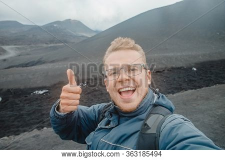 Tourist With Backpack Makes Selfie Photo On Background Of Volcano Etna, Sicily Italy