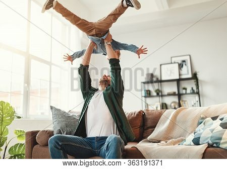 Cheerful Father Sitting On Sofa And Throwing Up Delighted Little Boy While Having Fun And Enjoying T
