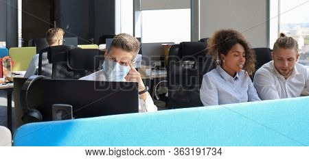 Businessman Is Working In Preventive Medical Mask In The Epidemic In Office, Collegues At The Backgr