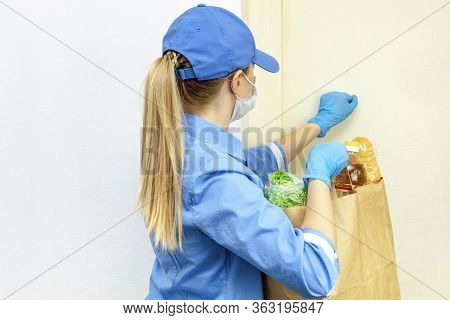 Volunteer Young Blonde Woman In A Uniform And A Medical Mask And Gloves Knocks On The Door And Holds