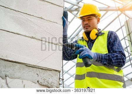 Mechanic Uses A Drill For Drilling Walls,builder Worker With A Drill  Machine For Drilling Aerated B