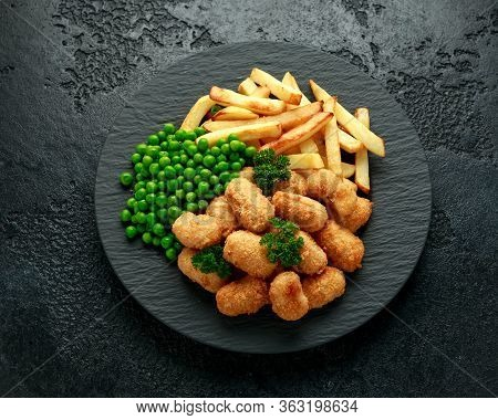 Crispy Battered Scampi Nuggets Served On Slate Plate With Potato Chips And Green Peas