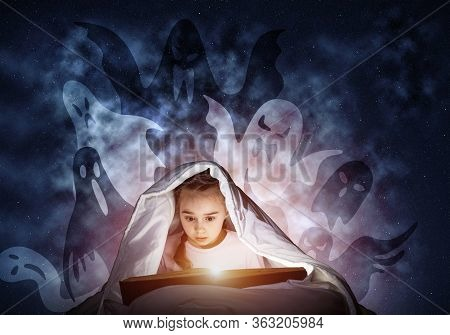 Enthusiastic Little Girl Reading Book In Bed After Bedtime. Kid In Pajamas With Flashlight Hiding Un