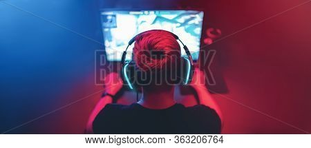 Blurred Background Professional Gamer Playing Tournaments Online Games Computer With Headphones, Red
