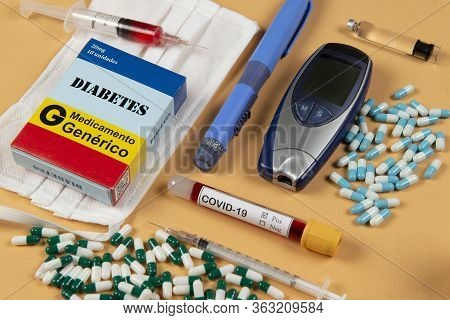 Various Elements Of Medicine On A Orange Background And A Tube Of Blood Test For Covid-19. Box Write