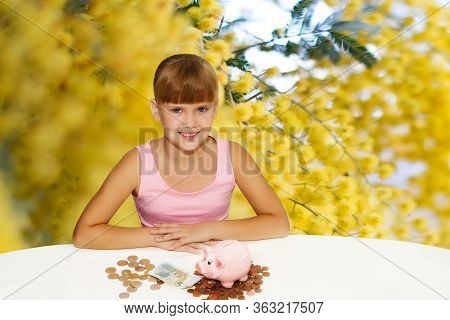 Little Lovely Girl With Coinsand Piggy Bank On The Desk Over Yellow Flowers Background. Saving Money