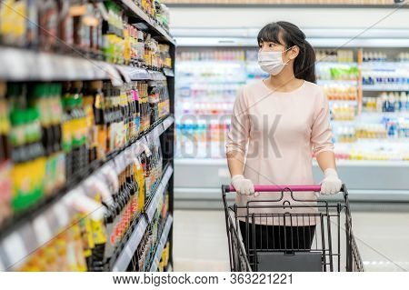 Asian Woman With Hygienic Mask And Rubber Glove With Shopping Cart In Grocery And Looking For Sauce