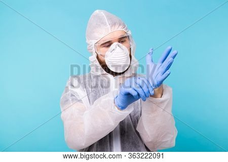 Professional For Disinfection Efforts. Epidemiologist Man Puts On Protective Suit And Gloves. Corona