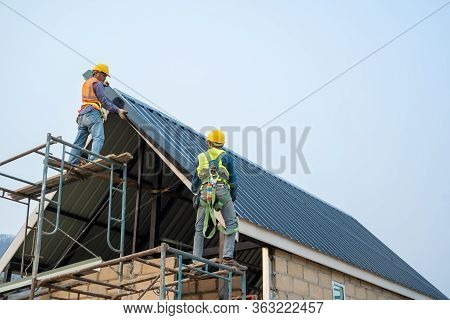 Roofer Using Air Or Pneumatic Nail Gun And Installing Metal Roof Tile On Top Roof,builder Working On