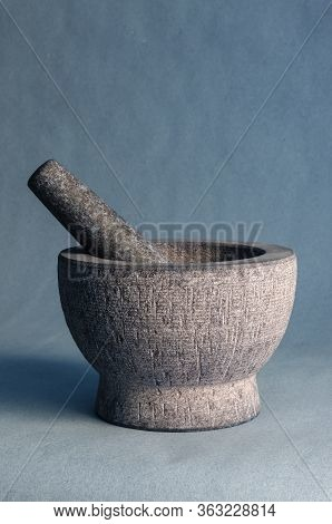 Gray Stone Mortar With Pestle. Close-up Of A Kitchen Granite Mortar On A Blue Background. Copy Space