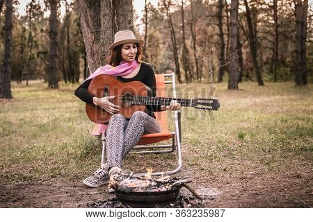 Woman Paying Guitar In Nature. Happy People Lifestyle. Woman Relaxing With Guitar In Nature. Nature
