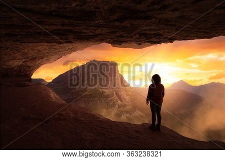 Adventurous Girl Looking Out At A Dramatic American Mountain Landscape From A Rocky Cave During A Co