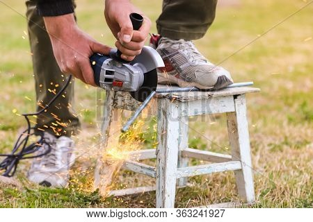 Man Holds Angle Grinder With Hands And Cuts Metal Tack, Sparks From The Tool.