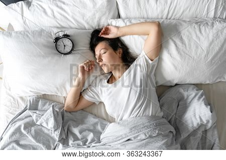 Top View Of A Girl Sleeping Next To An Alarm Clock. Time To Wake Up. On The Wake-up Clock 7 A.m. Dee