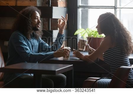 Multiracial Couple Talk On Date In Cozy Coffeehouse