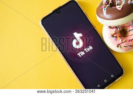 Tver, Russia-april 9, 2020, The Tik Tok Logo On A Smartphone Screen On Yellow Background With Donats