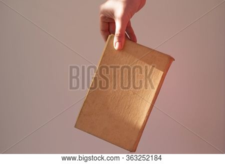 Book In The Hand Of A Girl With A Beautiful Shadow On A White And Gray Background. Beige Book In Han