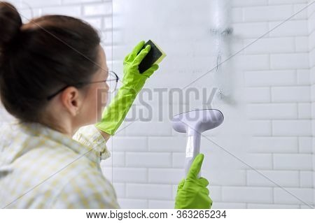 Woman Housewife Doing House Cleaning In Bathroom, Female Washing Glass With Shower Steam. Using Stea
