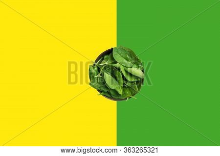 Fresh Raw Spinach Leaves In Bowl On Duotone Yellow Green Background. Healthy Plant Based Diet Detox