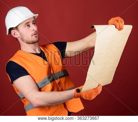 Architect Concept. Engineer, Architect, Builder On Strict Face Holds Old Blueprint In Hands, Supervi
