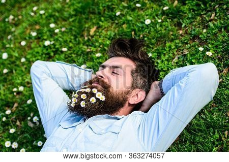 Spring Holiday Concept. Hipster On Happy Face Lays On Grass. Macho With Beard And Mustache Enjoys Sp