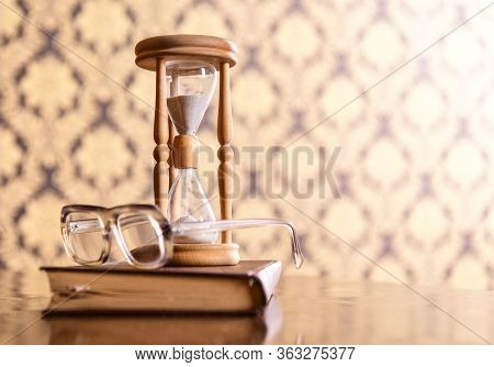 Old Fashioned Attributes Concept. Hourglass, Old Book And Eyeglasses On Wooden Table, Pattern Backgr