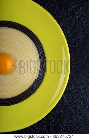 Half Of Olive Color Plate With Black And White Linguini Pasta With Egg Yolk In The Middle. Top View