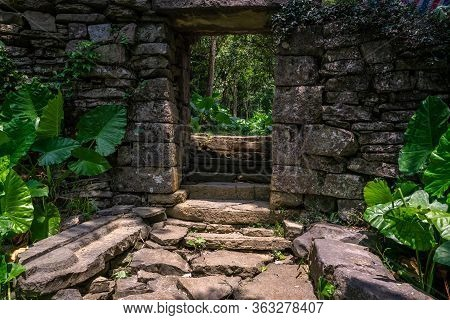 Entrance Gate To The Empty, Ruined And Overgrown By Tropical Plants Ancient And Old Abandoned Houses
