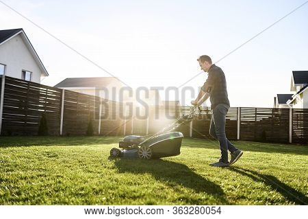 Spring Mowing The Lawn. Young Man In A Plaid Shirt And Jeans Mows Grass With A Lawn Mower In The Bac