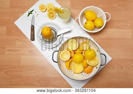 High angle shot of the equipment to make fresh homemade lemonade. With a colander full of juiced rinds.