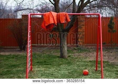 Two Ginger Red Jakets Hand On A Soccer Gate, Togetherness Without People Concept