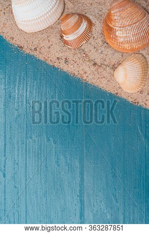 Golden Beach Sand With Seashells On A Blue Wooden Background. Summer Travel Abstract Concept. Copy S
