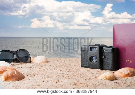 Passport, Vintage Film Camera, Sunglasses And Seashells On Golden Beach Sand. Summer Travel Abstract