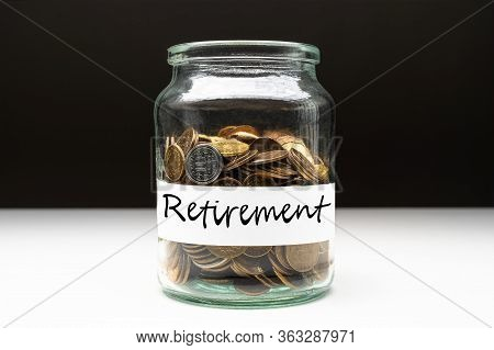 Coins In A Jar With Retirement Text On A White Label. Savings Abstract Concept. Copy Space.