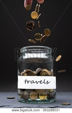 Coins In A Jar With Travels Text On A White Label. Caucasian Man Throwing Money From Above. Savings