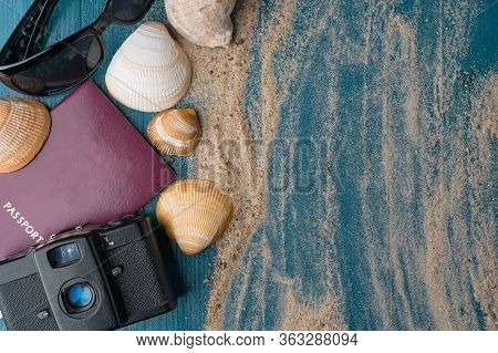 Passport, Vintage Film Camera, Sunglasses And Seashells On A Blue Wooden Background With Golden Beac