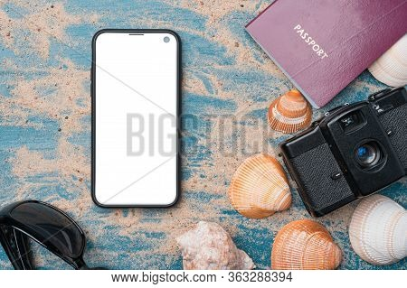 Bezel-less Smartphone, Passport, Vintage Film Camera, Sunglasses And Seashells On A Blue Wooden Back