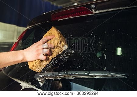 Glass Car Door With Foam And A Hand With A Foam Sponge