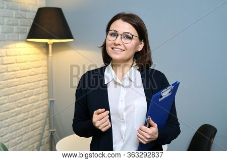 Mature Woman Psychologist, Psychiatrist, Social Worker With Clipboard Looking At Camera, Background