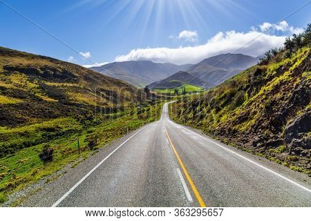 The magic of New Zealand. New Zealand Southern Alps. The road to the city of Cromwell among the mountains and meadows. Blue sky and light clouds. The concept of ecological and photo tourism