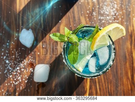 Blue Alcoholic Cocktail In A Glass On A Wooden Bar Counter