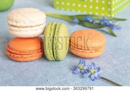 Multi-colored Macaroons And Spring Flower On A Linen Napkin. Macarons Or Macaroons Is French Or Ital