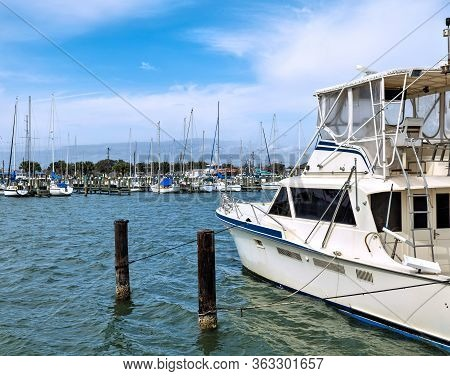White Pleasure Motor Boat Is Tied By Ropes To Wood Pillars In The Water In A Marina With Many Sailbo