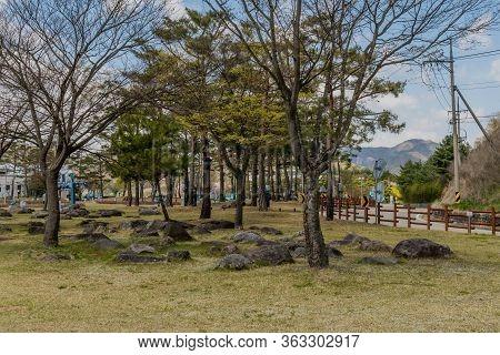 Jinan, South Korea; April 21, 2020: Boulders Under Trees In Yongdam Dam Reservoir Park With Building