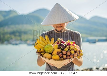 Variety Of Fruits In A Vietnamese Hat. Man In A Vietnamese Hat