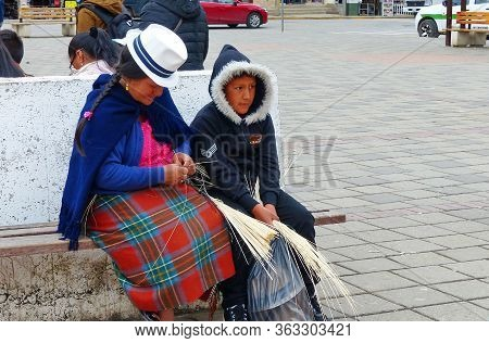 Cuenca, Ecuador - September 22, 2018: Indigenous Woman From Ecuador With Son Sit On The Bench At Par