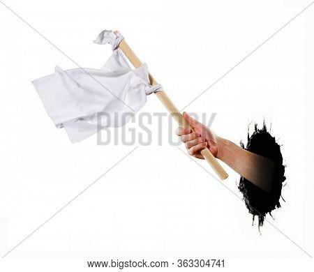 Hand hold white flag from dark hole asking help.