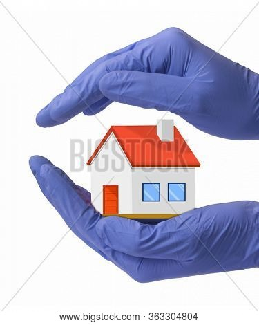Doctor hand hold and protect mini model house with surgery gloves.